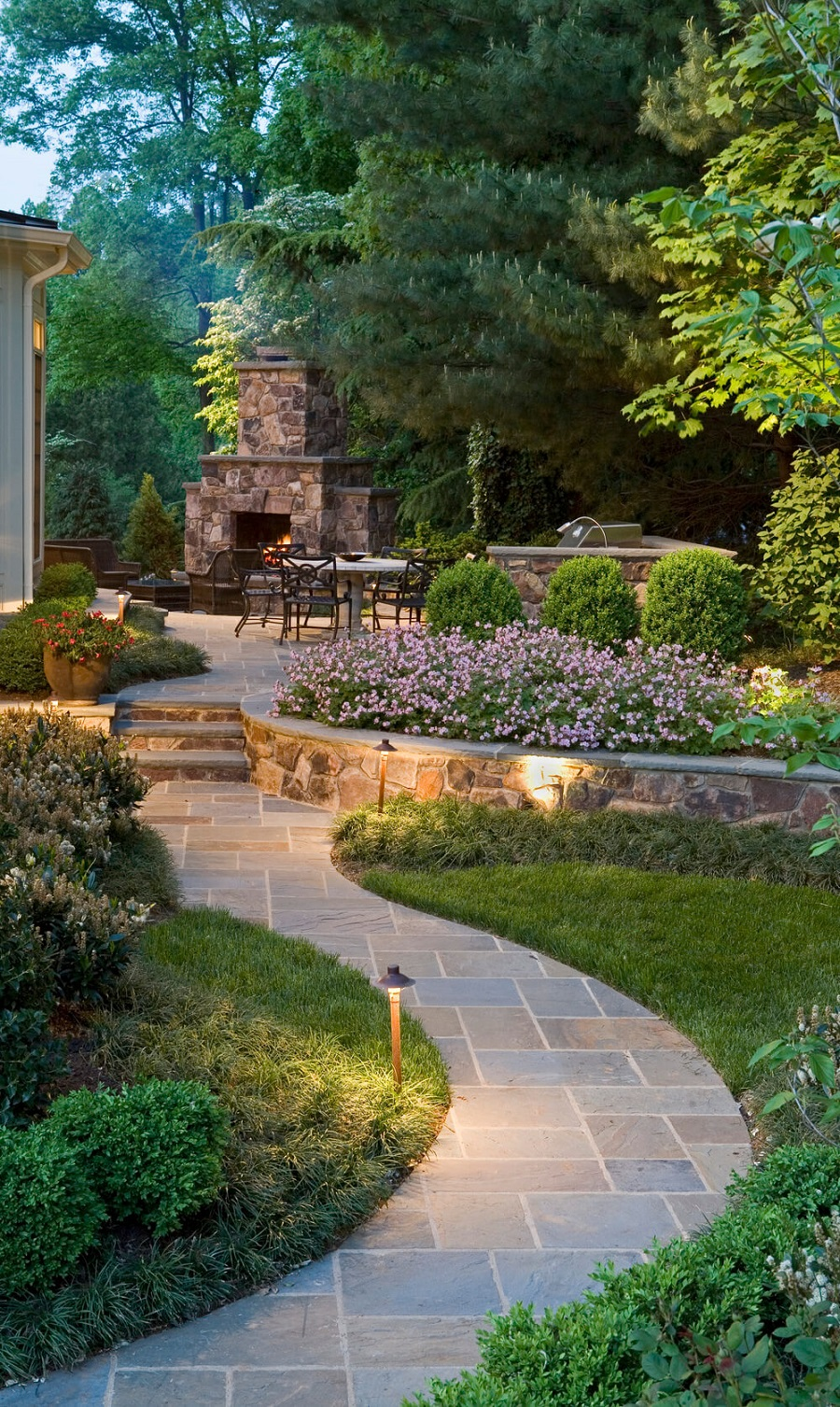 Outdoor fireplace with landscape lighting in Newington, CT