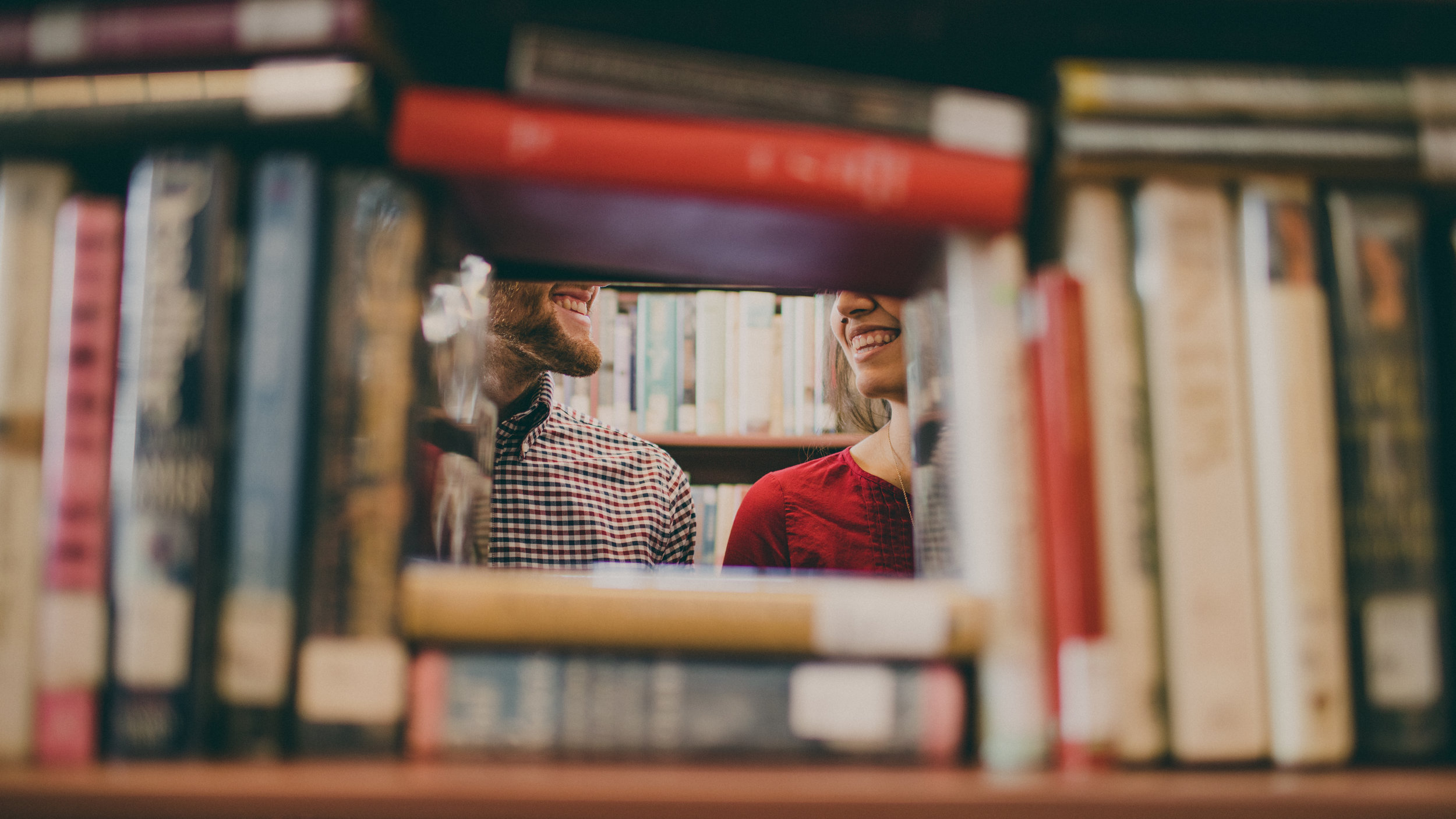 stacks of books with a man and woman smiling at eachother
