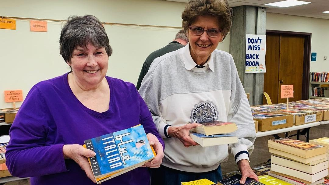 Two+older+women+smiling+and+sorting+books