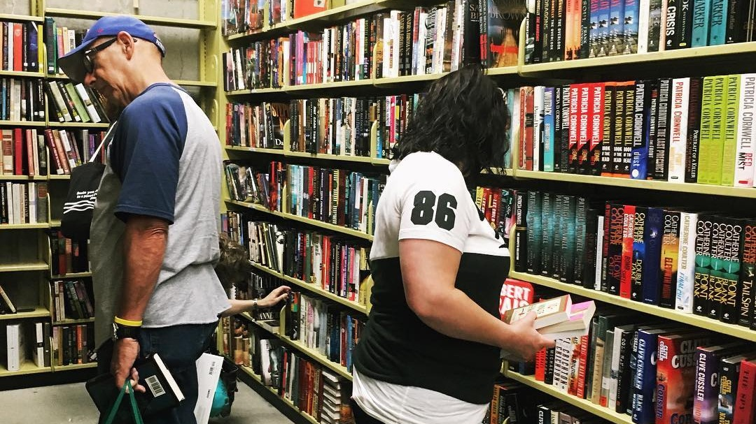 people looking at books on a shelf