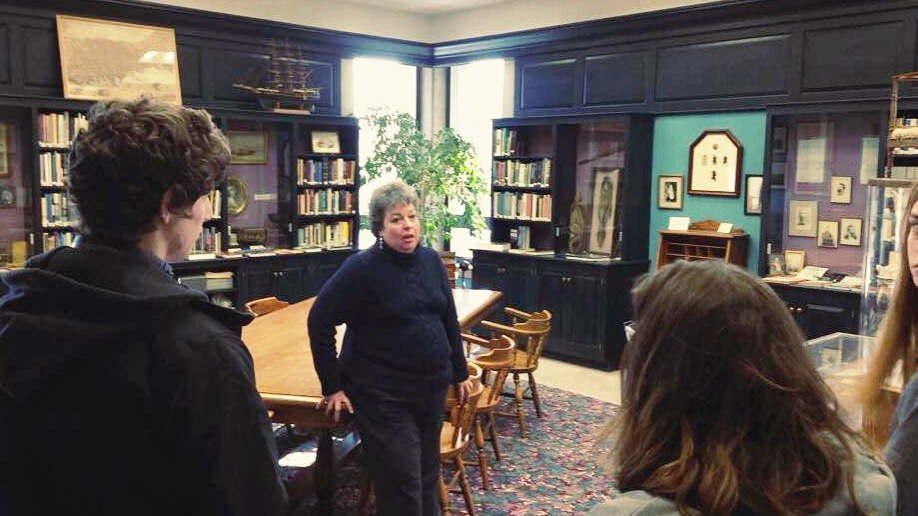 Group of students in Herman Melville Memorial Room learning about local history