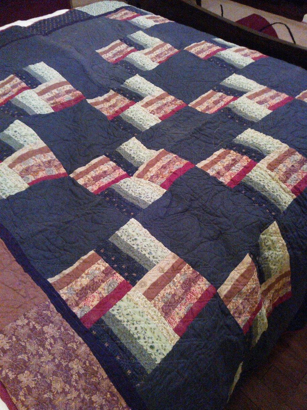My first completed quilt, a partially hand pieced, all hand quilted log-cabin pattern variation.