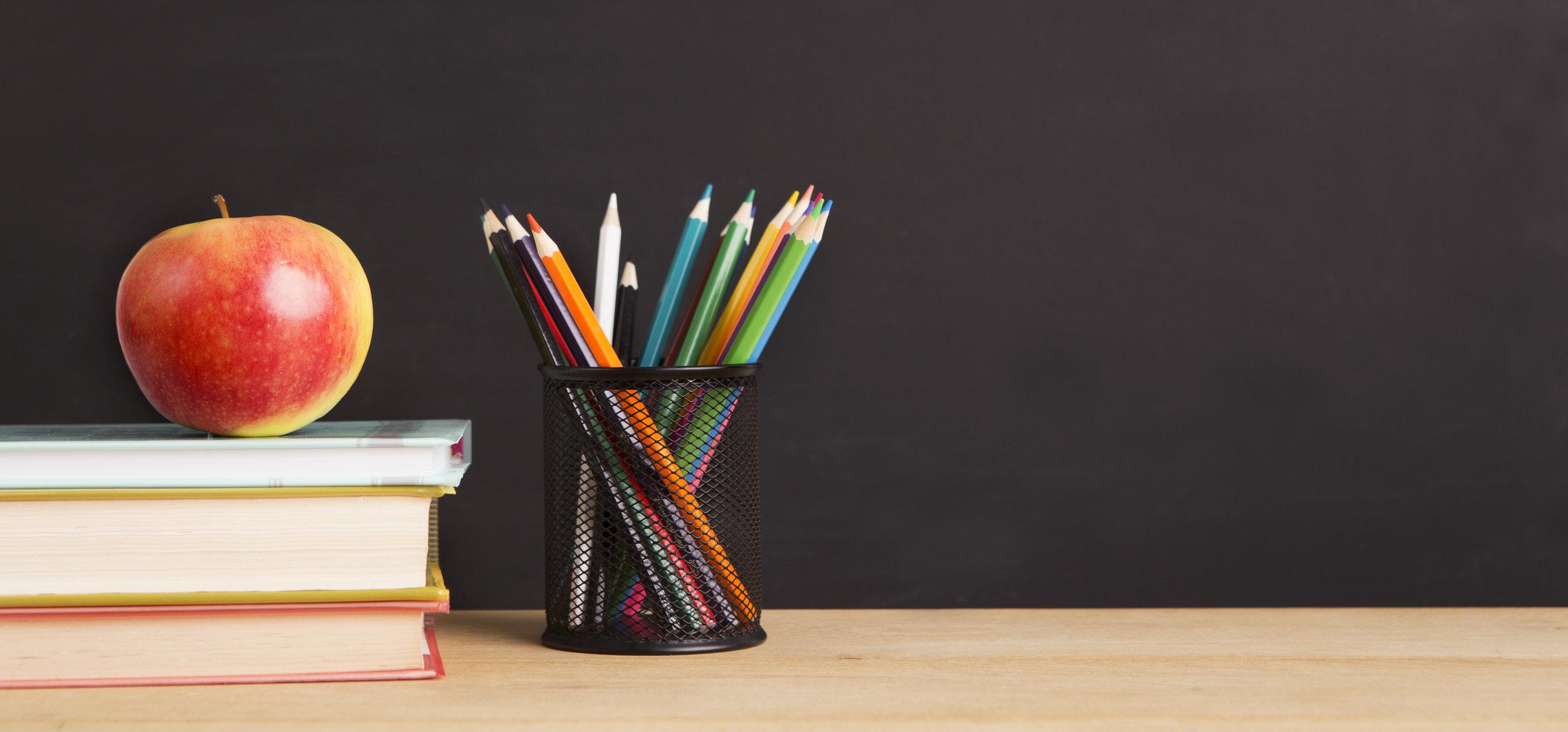 school-books-apple-and-pencils-over-chalkboard-BHWXCMU.jpg