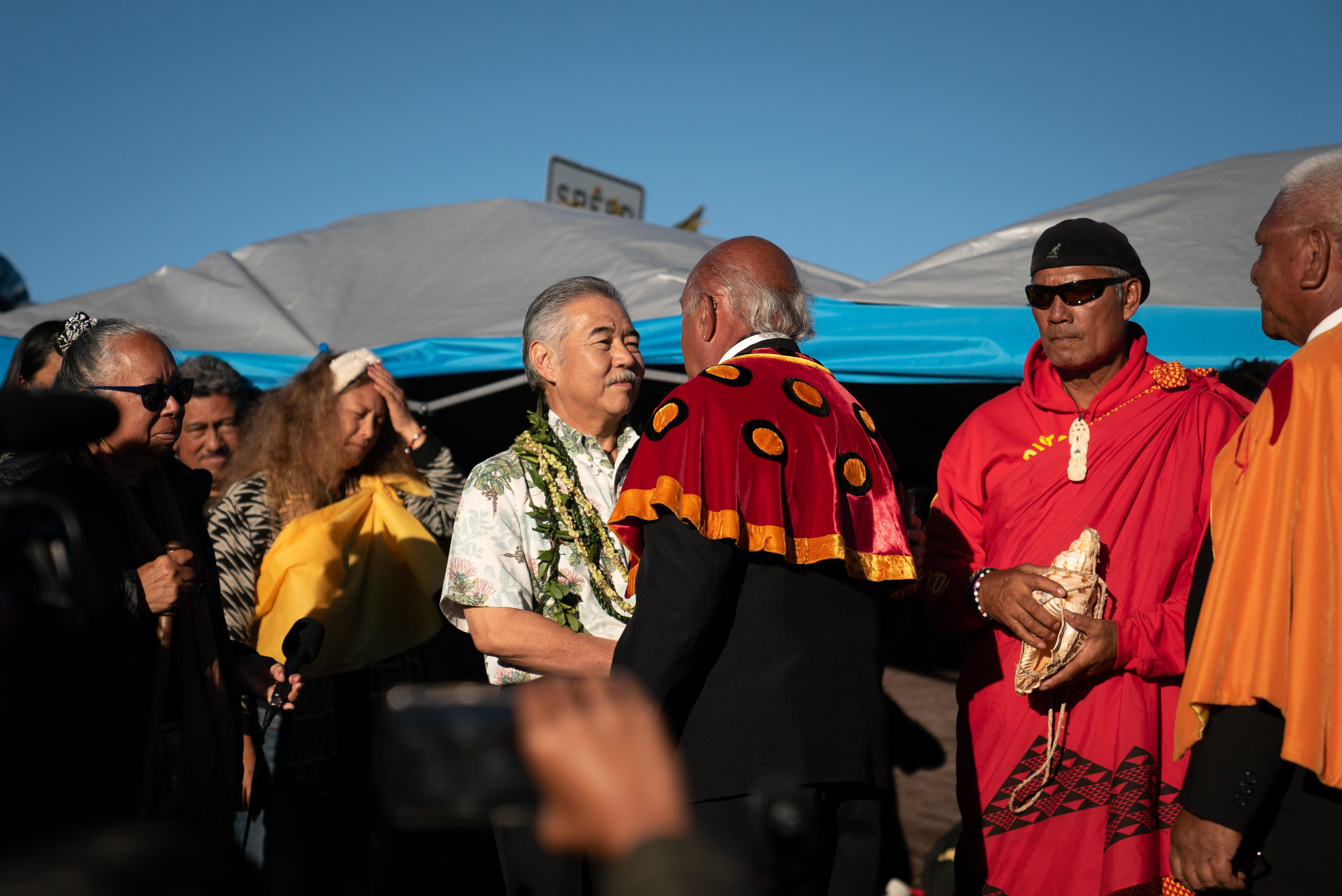 Governor David Ige arrives on the mountain after declaring a state of emergency and is greeted by the Royal Order of Kamehameha.