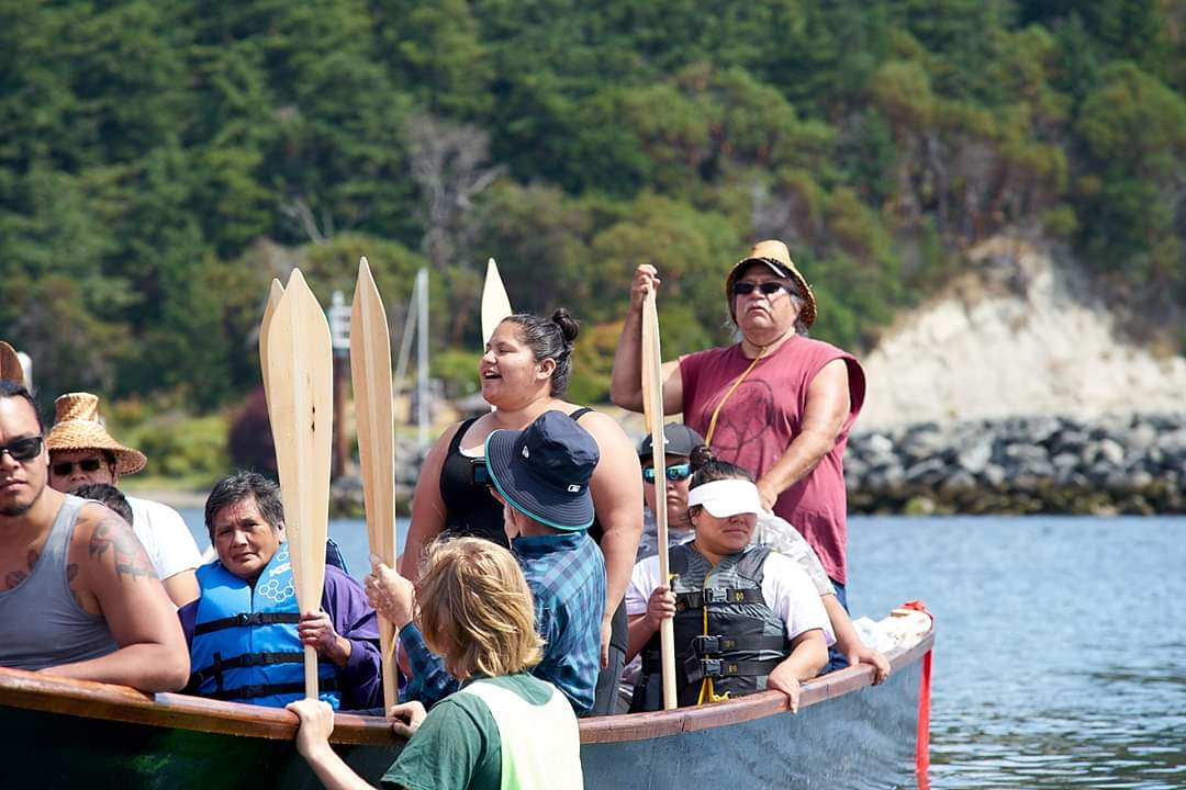 Nooksack Elder George Adams, at right, and his daughter Elile Adams, at center, during a 2019 Canoe Journey landing