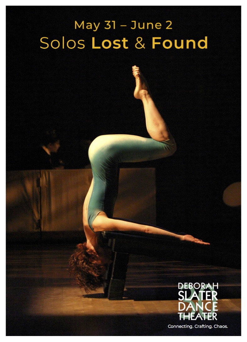 Jennifer Kesler balances upside down on the edge of a slanted table in a shoulder stand. Her arms are stretched long on top of the table. Her head drops to look under. And her torso raises to the sky - her legs in a seated right angle.