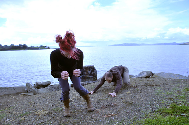Two dancers crouched low on dirt and rock near the water of the SF Bay.