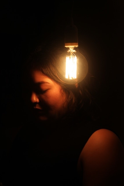 A close-up of a person's face illuminated by a single lightbulb agains a black background