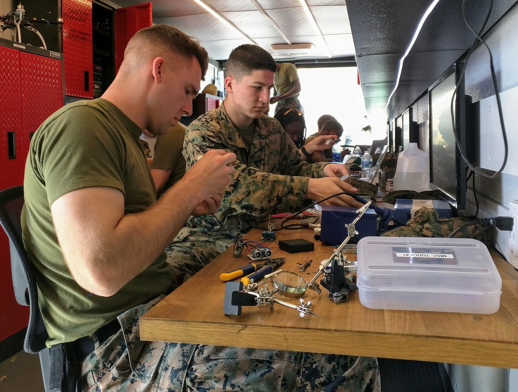 Figure 1. Marines soldering and programming Arduinos during Innovation Bootcamp in Building Momentum's mobile training lab.