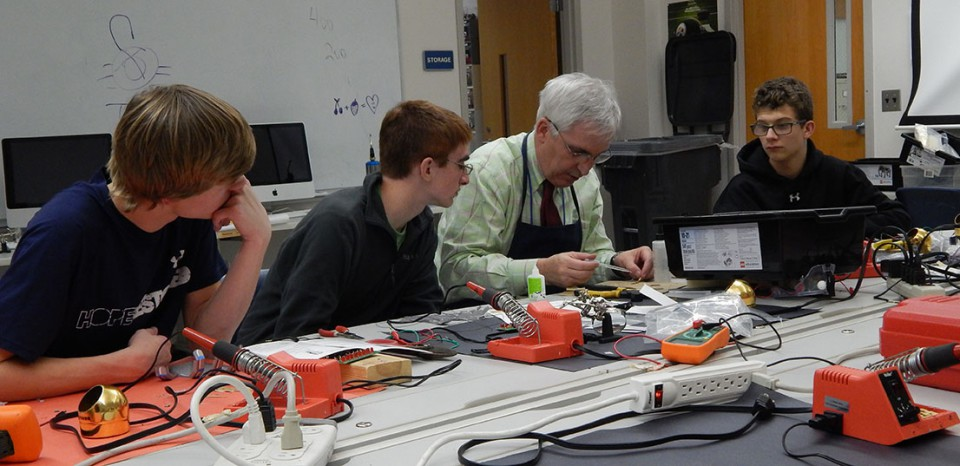 Tom Dubick teaching students about soldering.