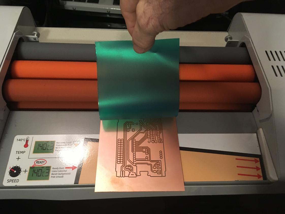 Laminating soldermask onto PCB.