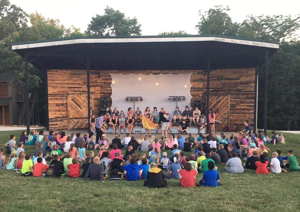 Outdoor Amphitheater - In addition to the pavilion, we also rent a large amphitheater area that is perfect for an evening of worship and praise. The stage was refinished in 2017 with pallet wood and edison bulb lights. It comes fully equipped with ample power for your worship band or concert. It also makes an ideal spot for an outdoor movie night!