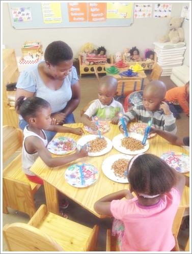 Teacher Maria works with three year olds on developing fine motor skills. Photo courtesy of Mary Jo Jean-Francois.