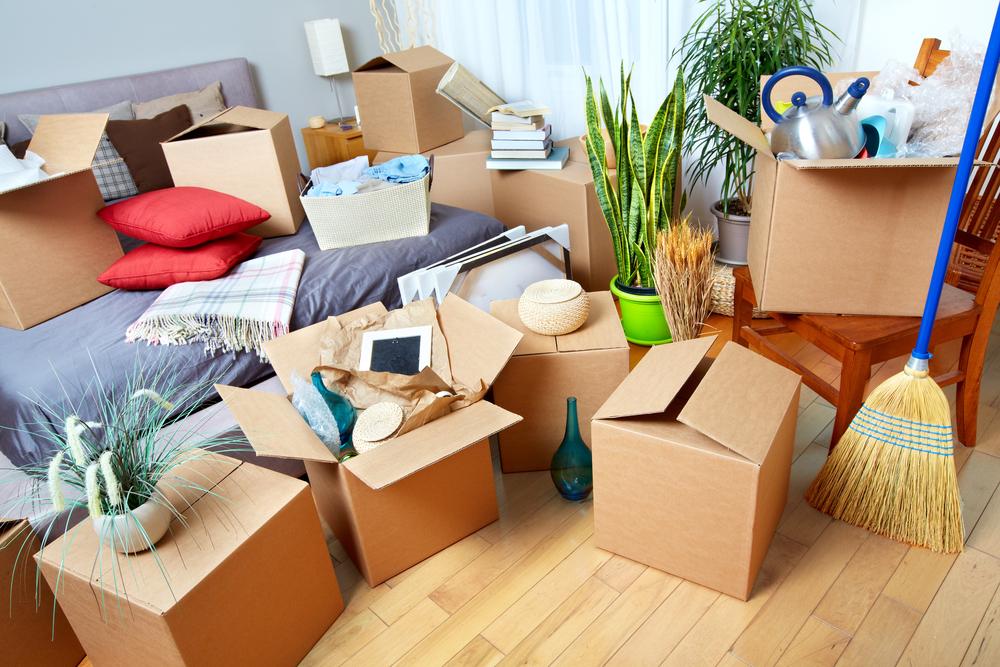 Verschillende verhuisdozen in een slaapkamer die uitpuilen met spullen.