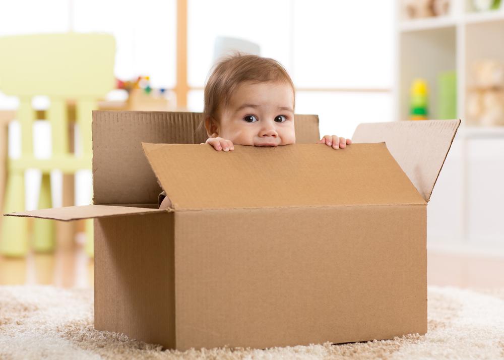 Een jong kind in een verhuisdoos.