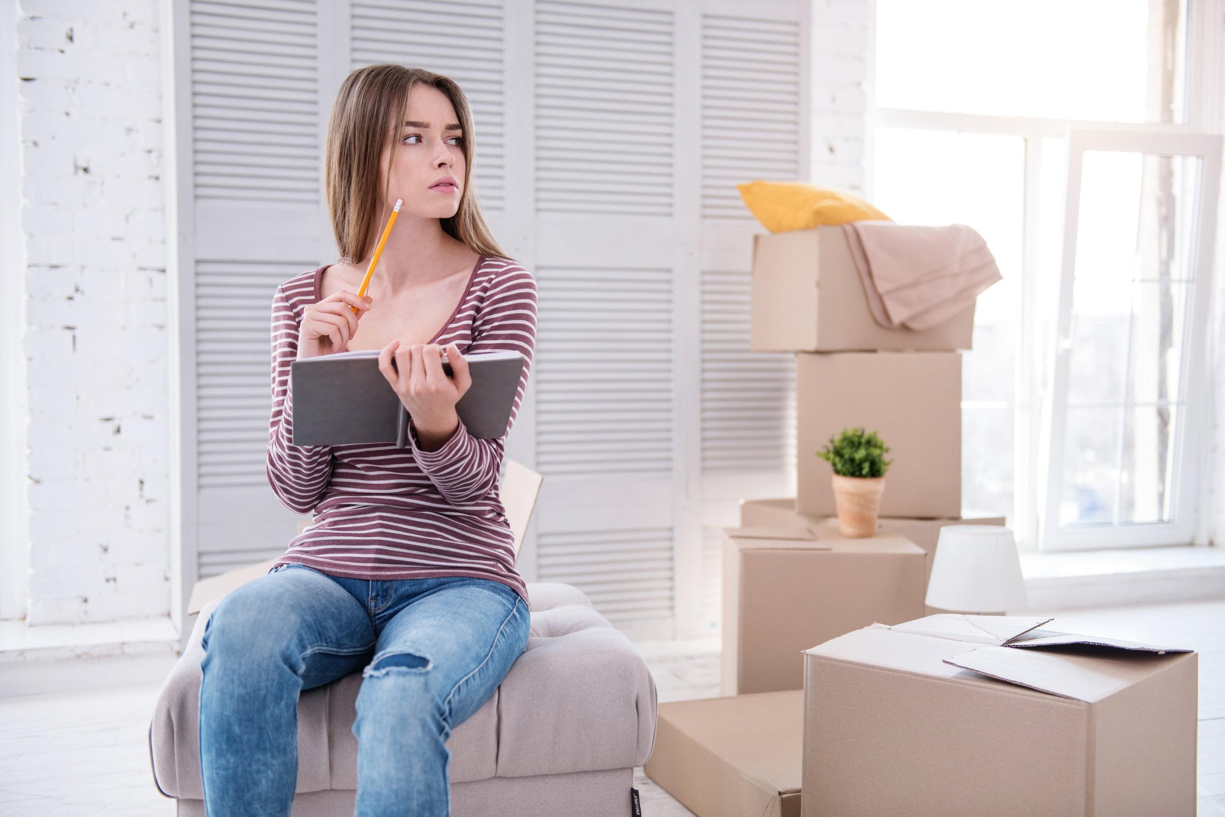 Een vrouw die op een stapel verhuisdozen zit en nadenkt over hoe ze haar adreswijziging moet doorgeven en aan wie.