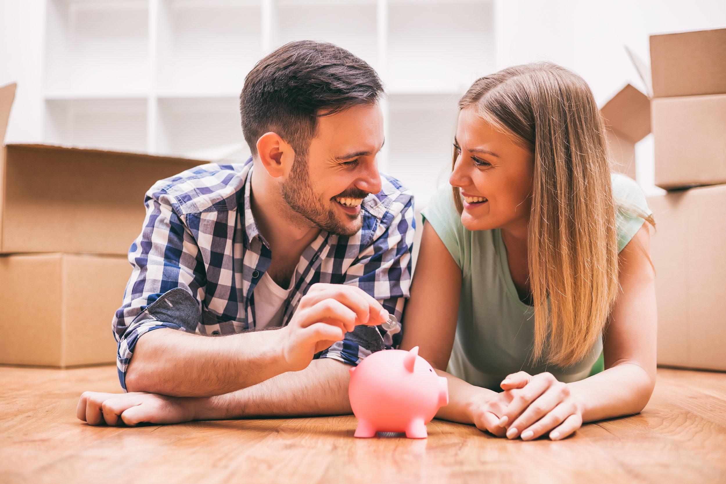 Een koppel dat op de grond ligt tussen een hoop verhuisdozen en een muntje in een spaarvarkentje steekt terwijl man en vrouw naar elkaar kijken.