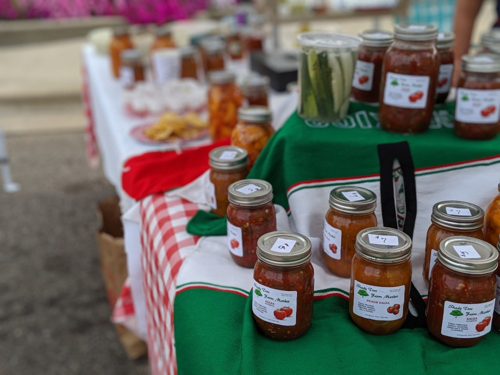 Jarred salsa and pickles on a table at the farmers market