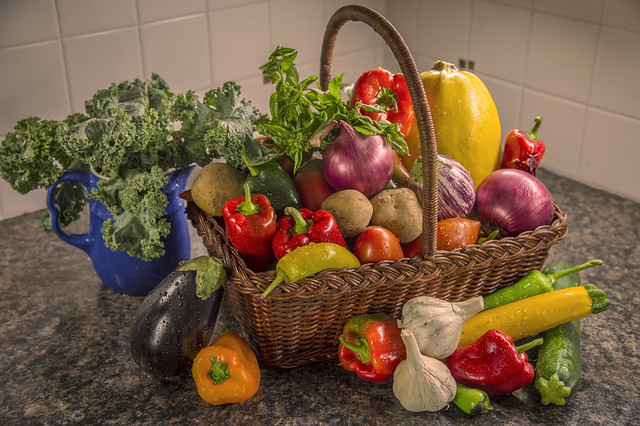 A variety of fresh produce in and surrounding a basket on a countertop