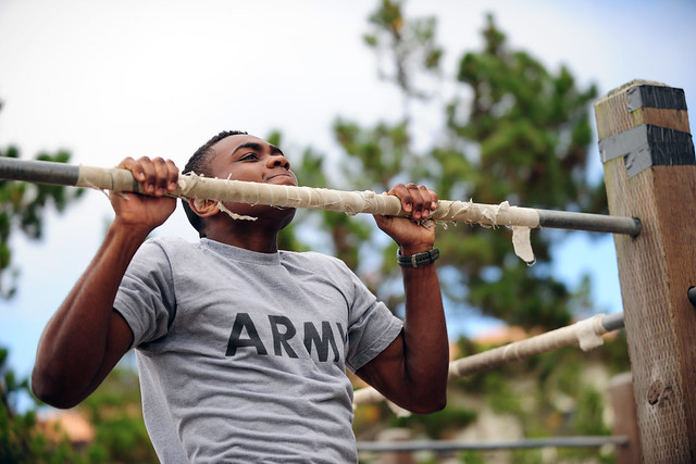 Person with dark skin presenting as male in an Army shirt doing a pull-up