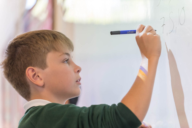School boy writing on white board