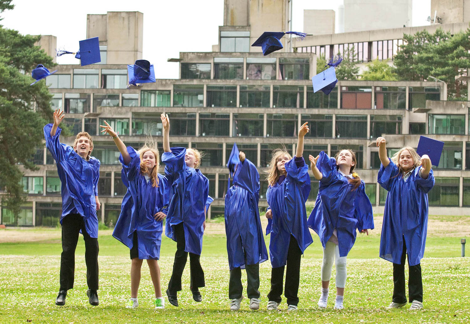 School children graduate and throw up their hats
