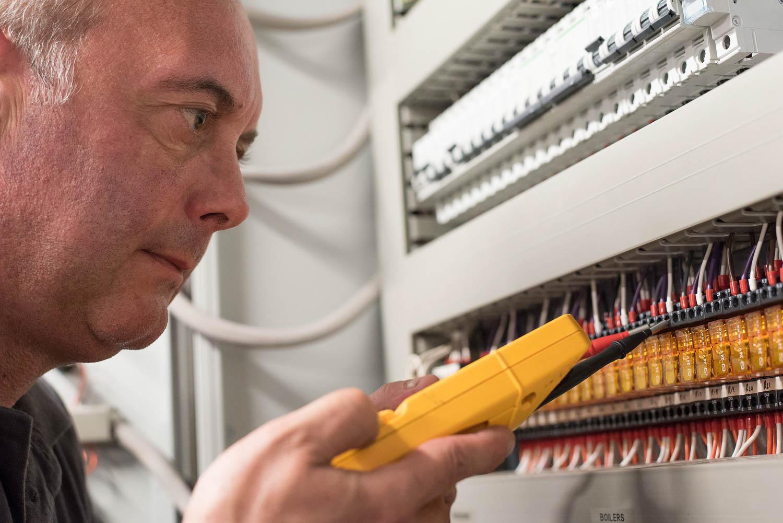 man testing electrical board