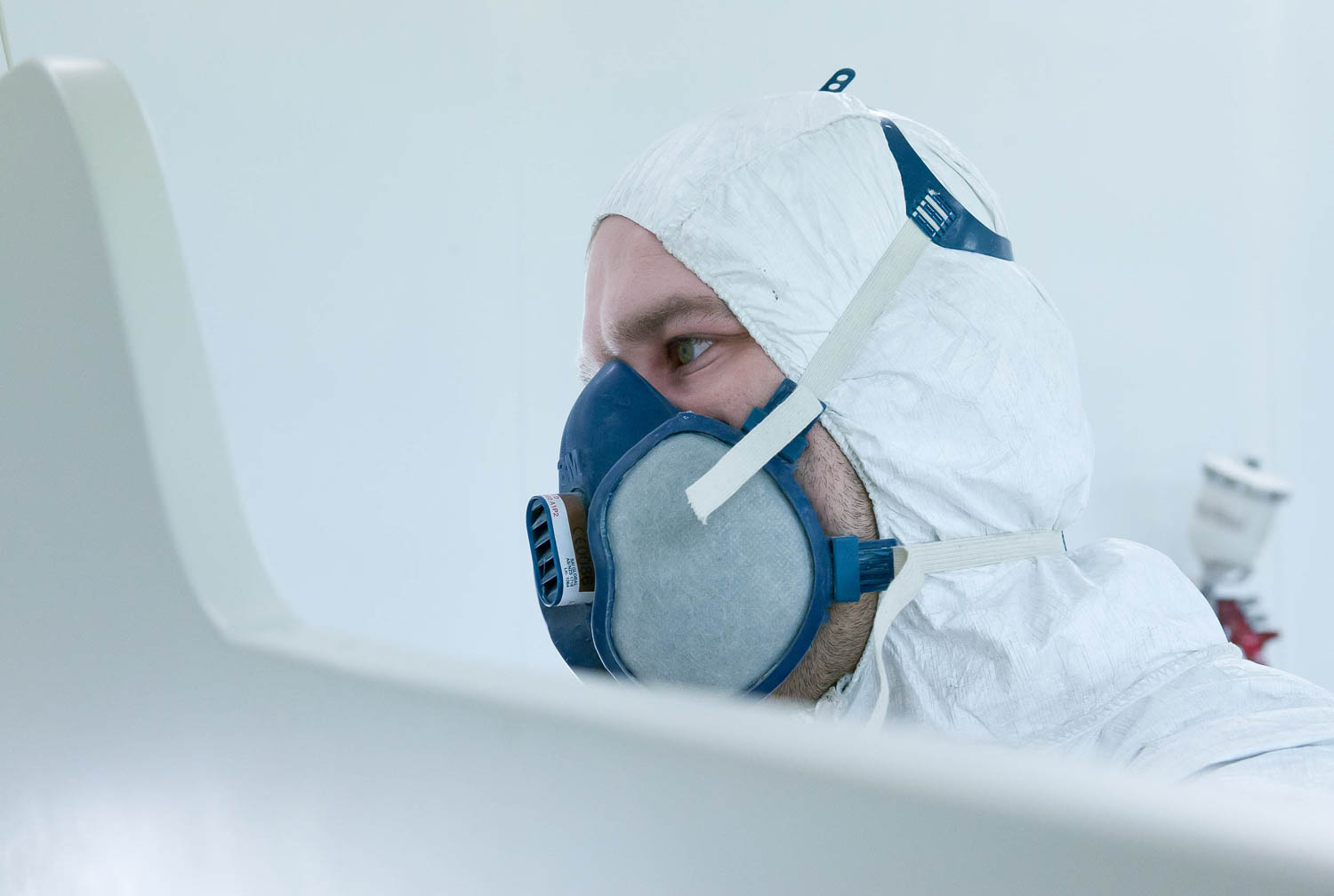 worker in mask and overalls painting