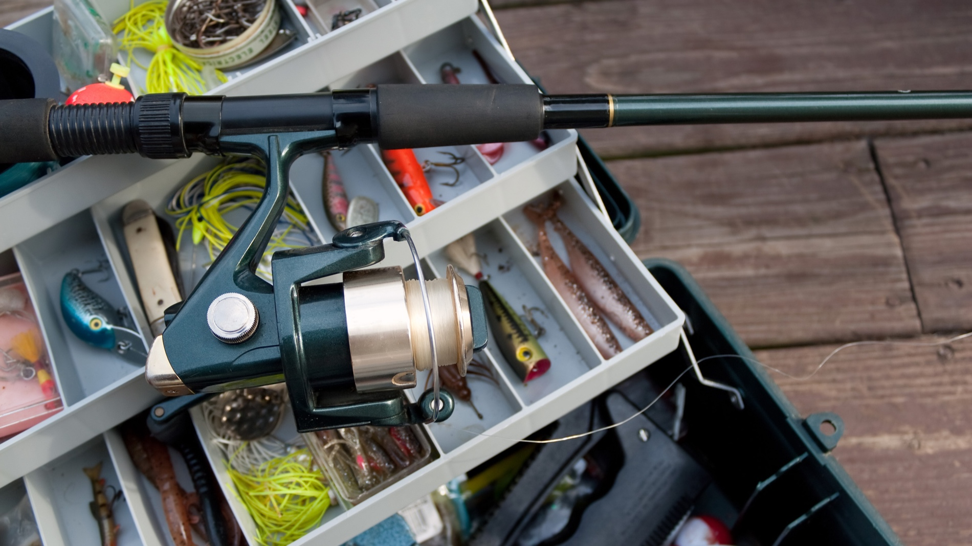 a-fishermans-rod-reel-and-tackle-box-filled-with-lures-and-bait-ready-for-the-start-of-fishing-season_SF85avCHi.jpg