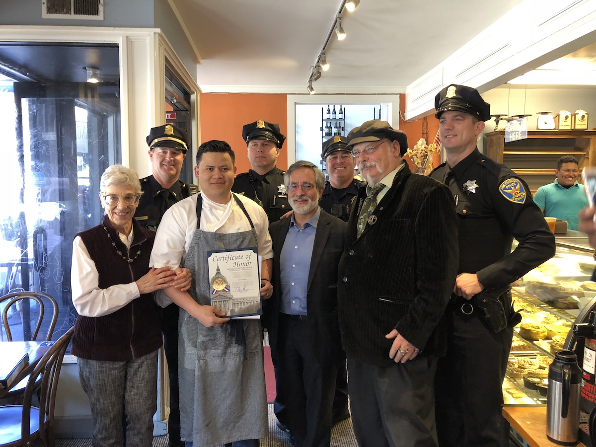 Supervisor Aaron Peskin and SFNBBA President Dan Macchiarini present Edson Garcia with commendations for bravery at his café on Columbus Avenue. | Photo: Sharli Colladay
