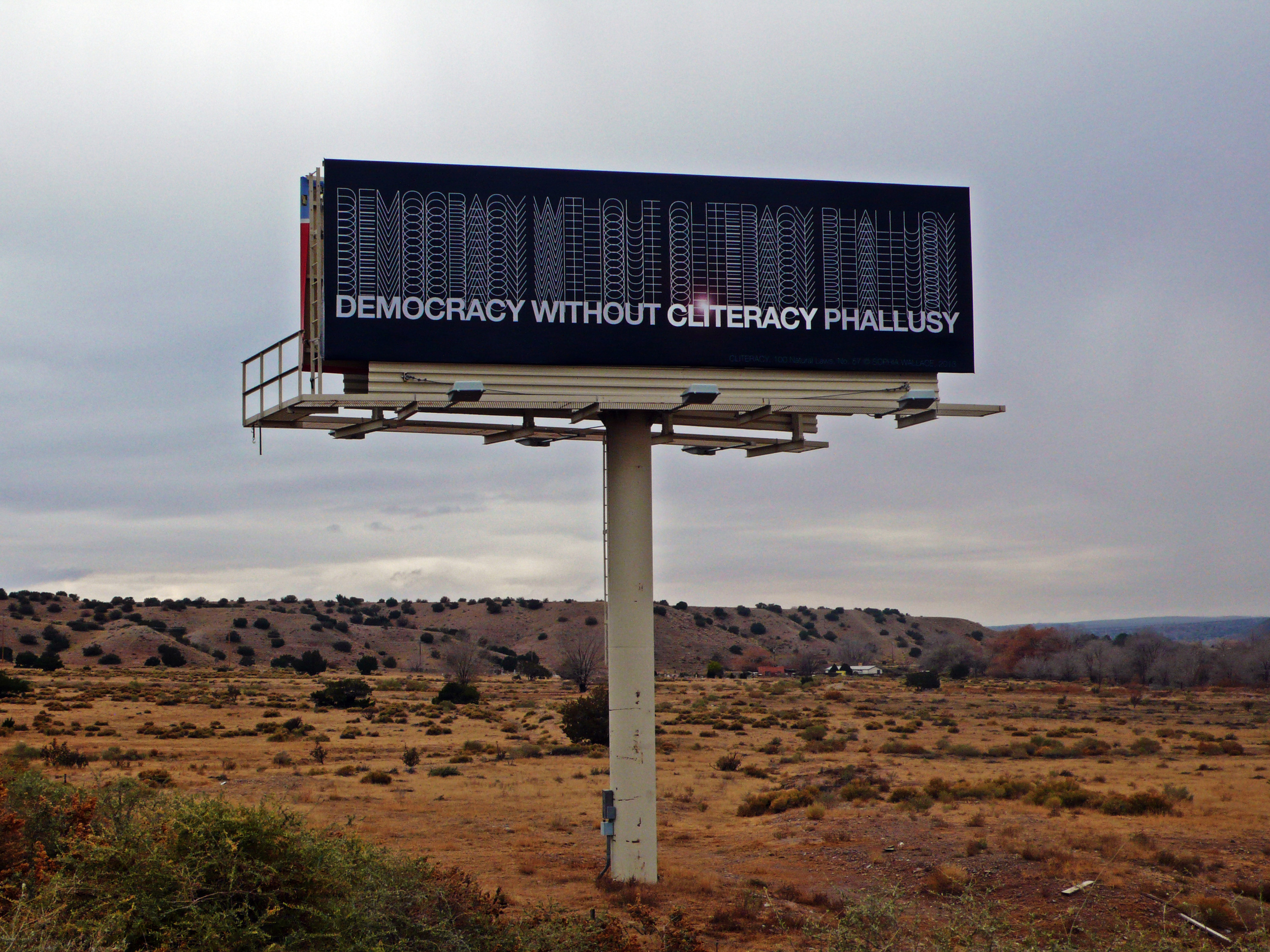 DEMOCRACY WITHOUT CLITERACY PHALLUSY,  Natural Law No. 57, 2013  Vinyl, Billboard 35 x 10.6 feet Exhibition on view November 11-25, 2013 on I-25 Southbound near mile marker 247.2.
