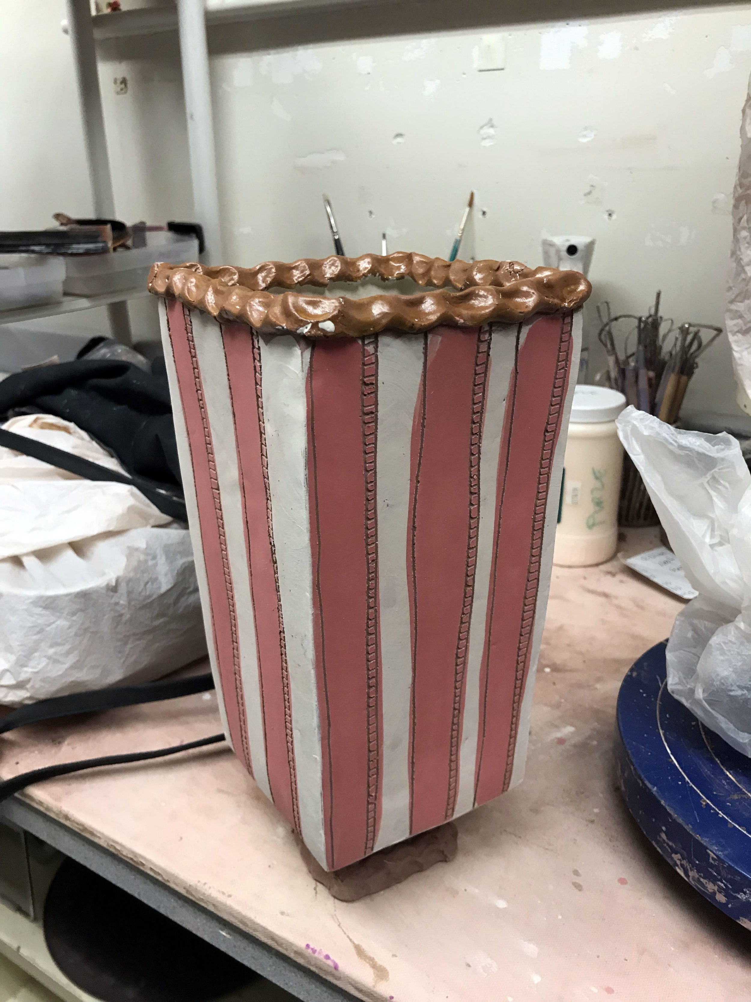 """Popcorn Anyone? - I have had this idea in my head for too long, and it has finally come to life. I wanted to make my own version of a """"free re-fill"""" popcorn bag. This vessel was slab constructed with pinched coils on the rim and built up on bottom to make an elevated foot. I am interested in how you can use something as simple as a LINE to guide a viewers eye in any direction you desire. In this case the viewers eye is drawn from top to bottom to rest on the texture of pinched coils, which actually resemble popcorn."""