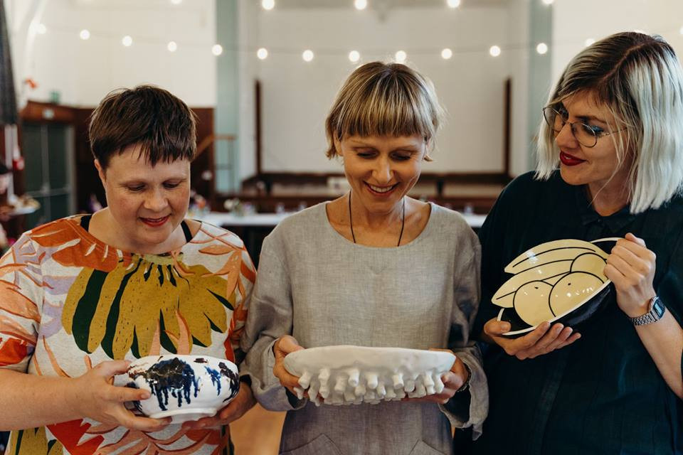 Heather Hayward, Abby Cunnane and Carmel Rowden, holding ceramics donated to the event. 2019.