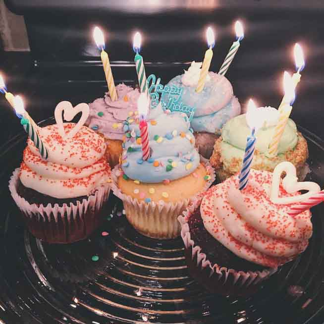 six-different-gourmet-cupcakes-with-lit-birthday-candles-sit-on-a-glass-platter-the-cupcake-in-the_t20_9l40xA.jpg