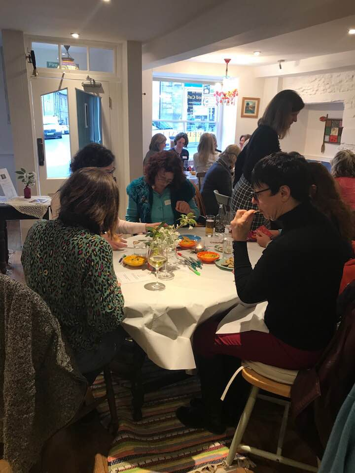 Women networking together while snacking on healthy snacks.