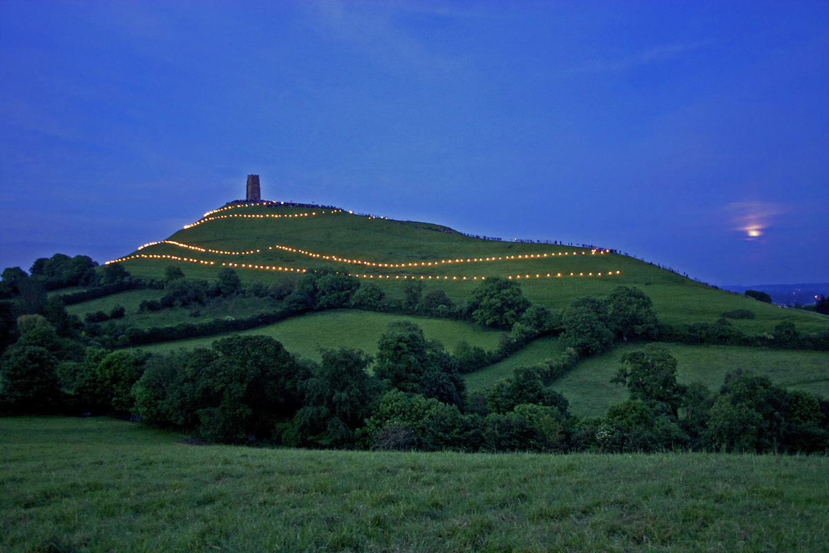 The magic of a June twilight and an emerging full moon. Glastonbury Tor lit up with flares at the Jubilee