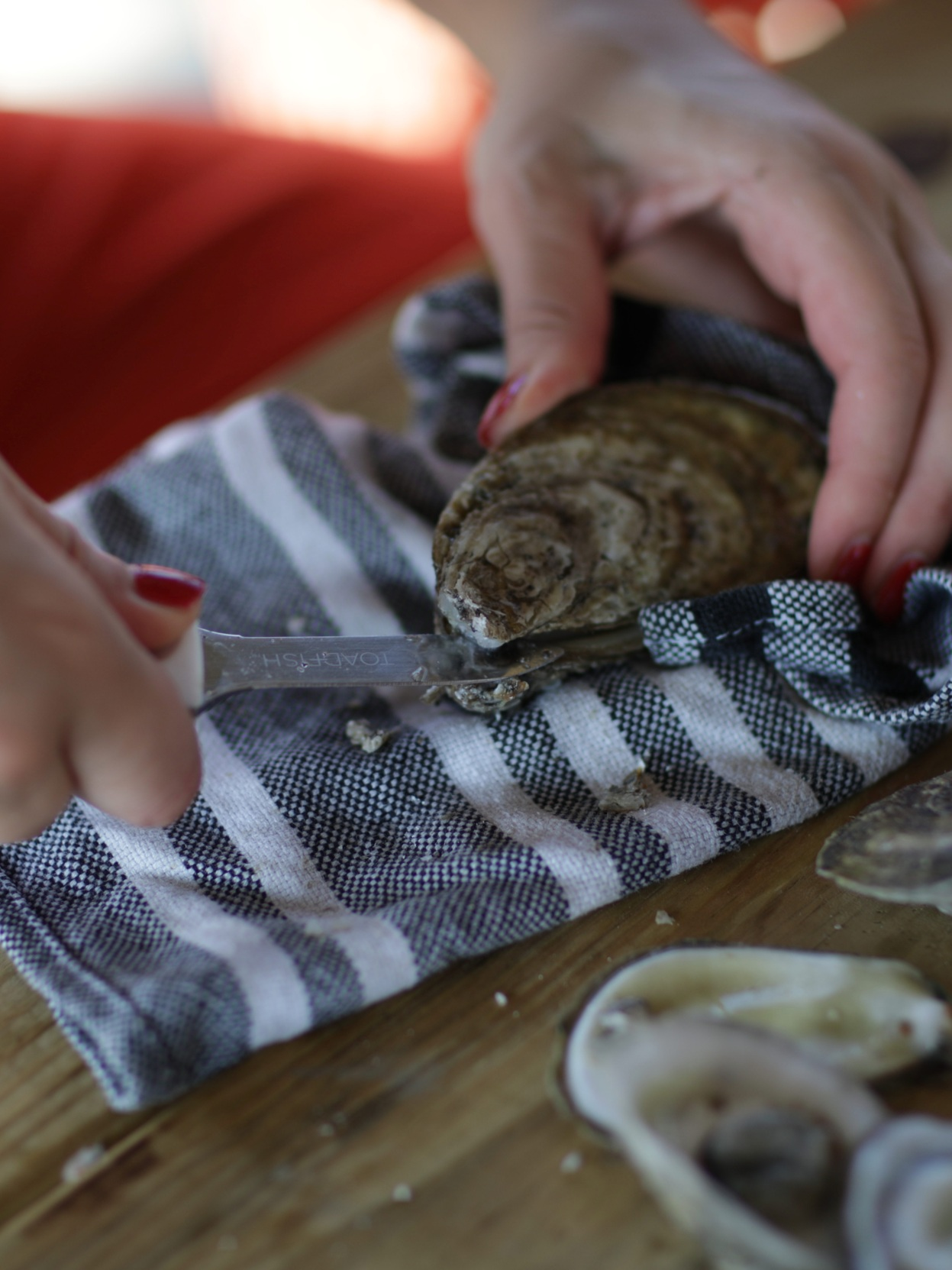 How to shuck an oyster: - 1. Roll a kitchen towel2. Place oyster hinge side down into the towel3. Wiggle the tip of the knife into the back hinge until you feel it unclasp4. Rotate your hand and feel the shell pop open5. Scrape the knife inside the top of the shell to unstick the oyster
