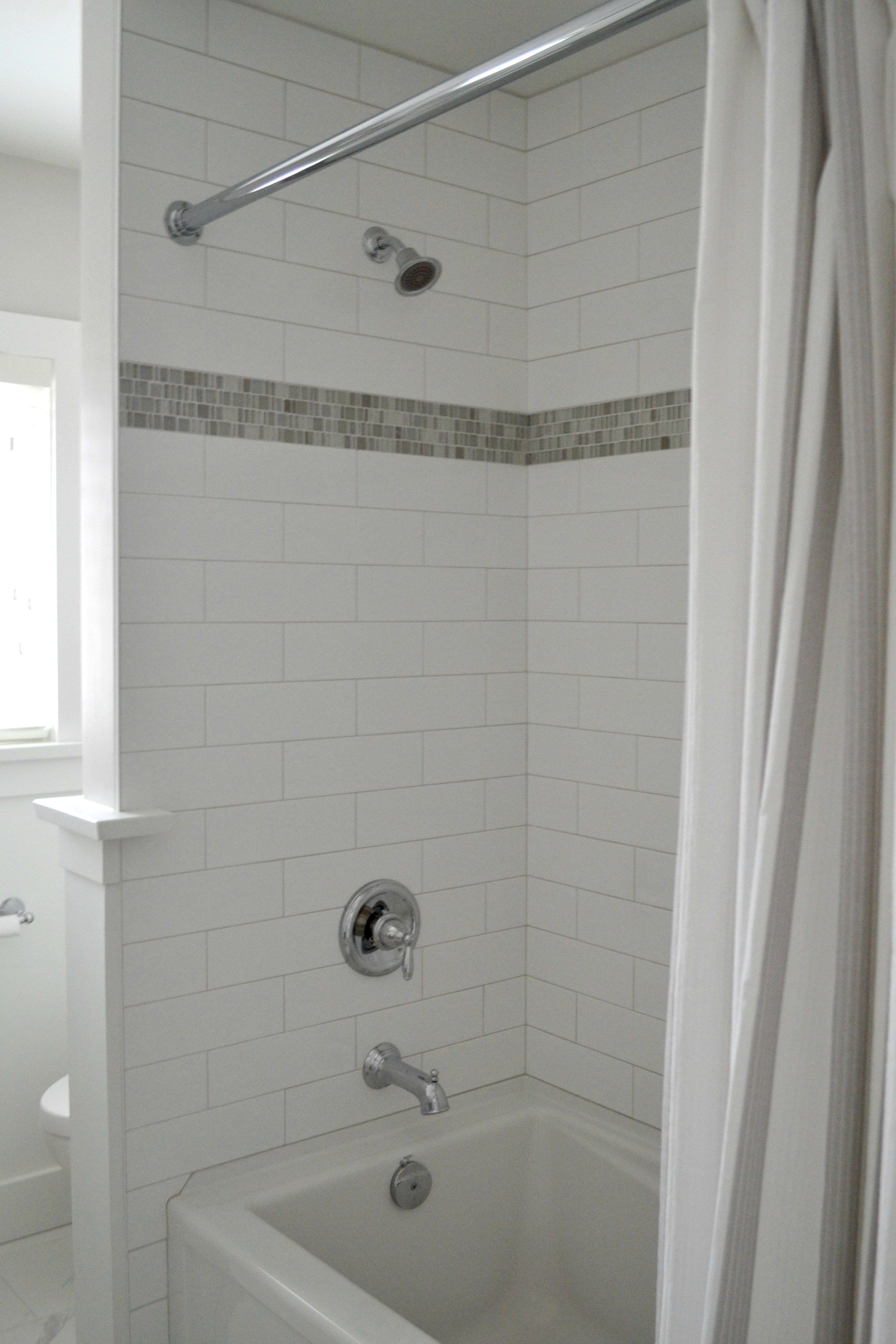 I used three different types of tile in this bathroom. The porcelain marble looking tile for the floor, the basic 3″ x 12″ white subway for the shower (my go to) and the mosaic for an accent tile.