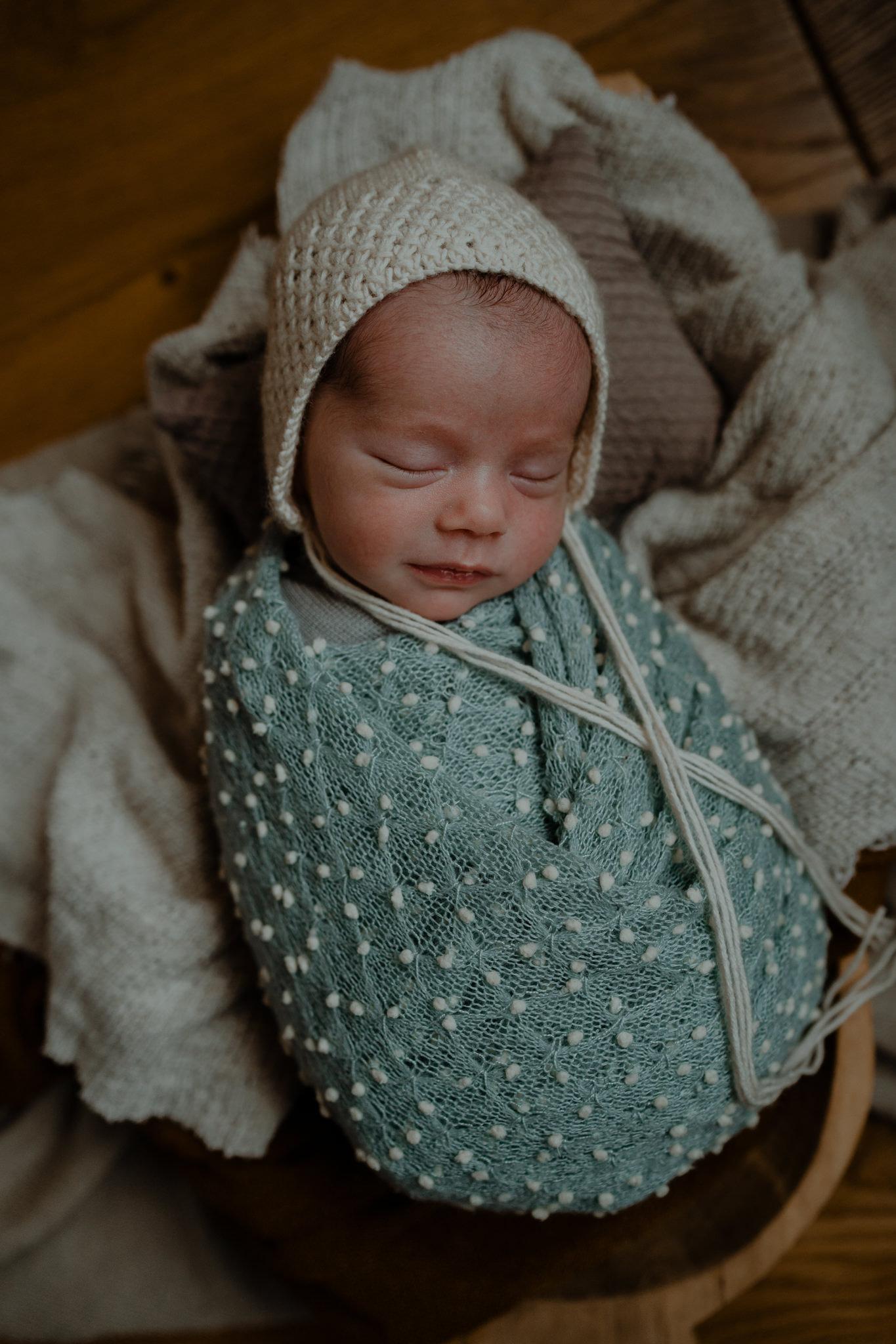 cute baby boy in bonnet and blue wrap