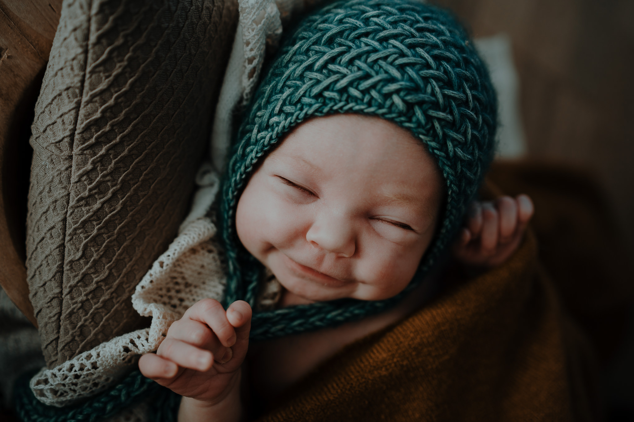 smiling-newborn-baby-teal-bonnet-in-home-belfast-photographer