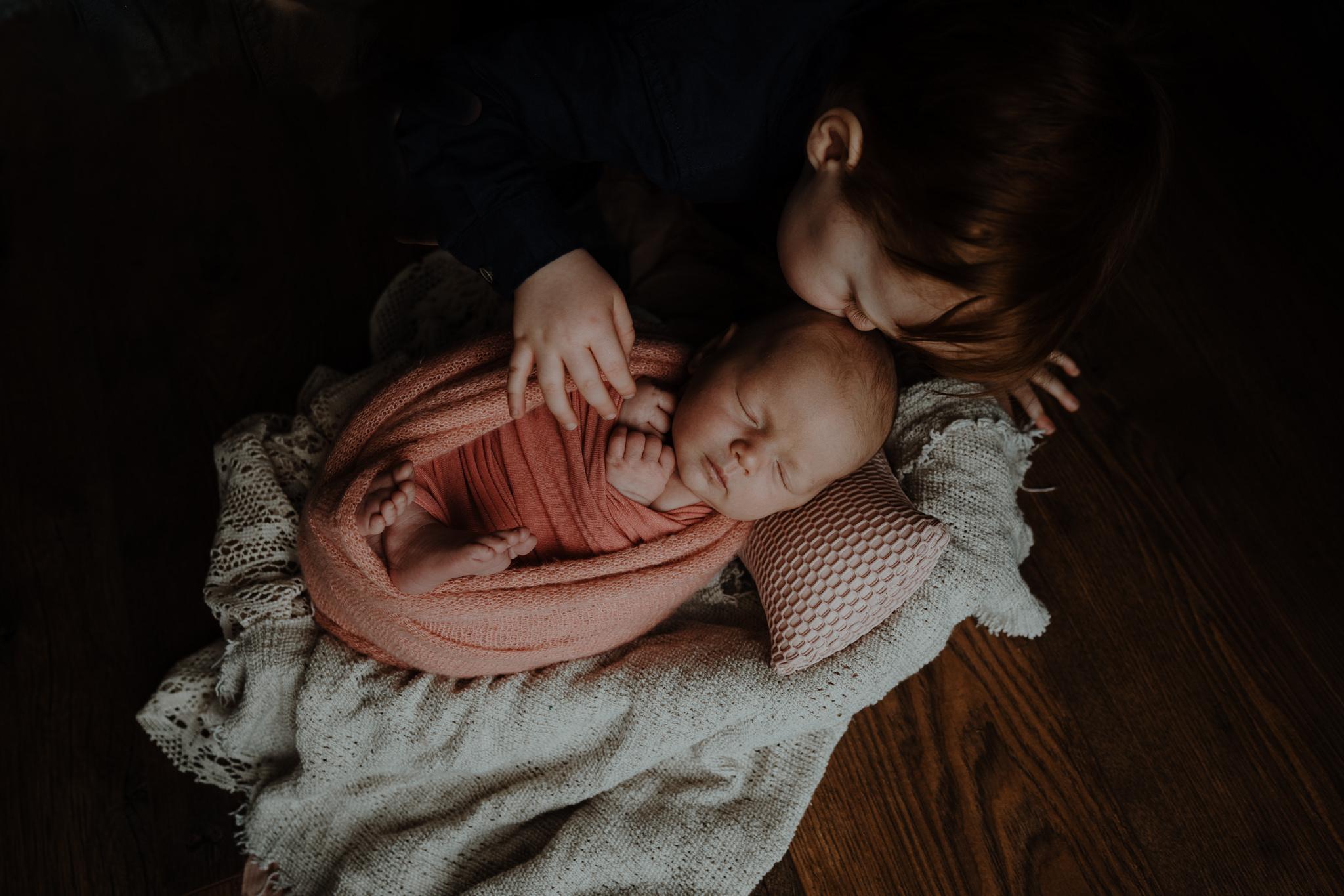 toddler-kisses-newborn-baby-sister-belfast-photograher
