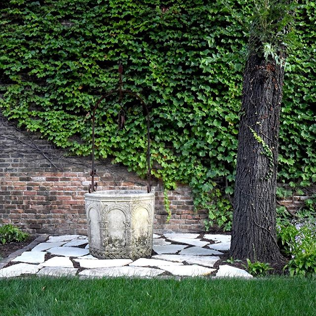 Ancient carved limestone well against a backdrop of Boston Ivy creates a timeless moment in this recently completed garden. #chicagolandscape #landscapearchitecture #landscapedesignbuild