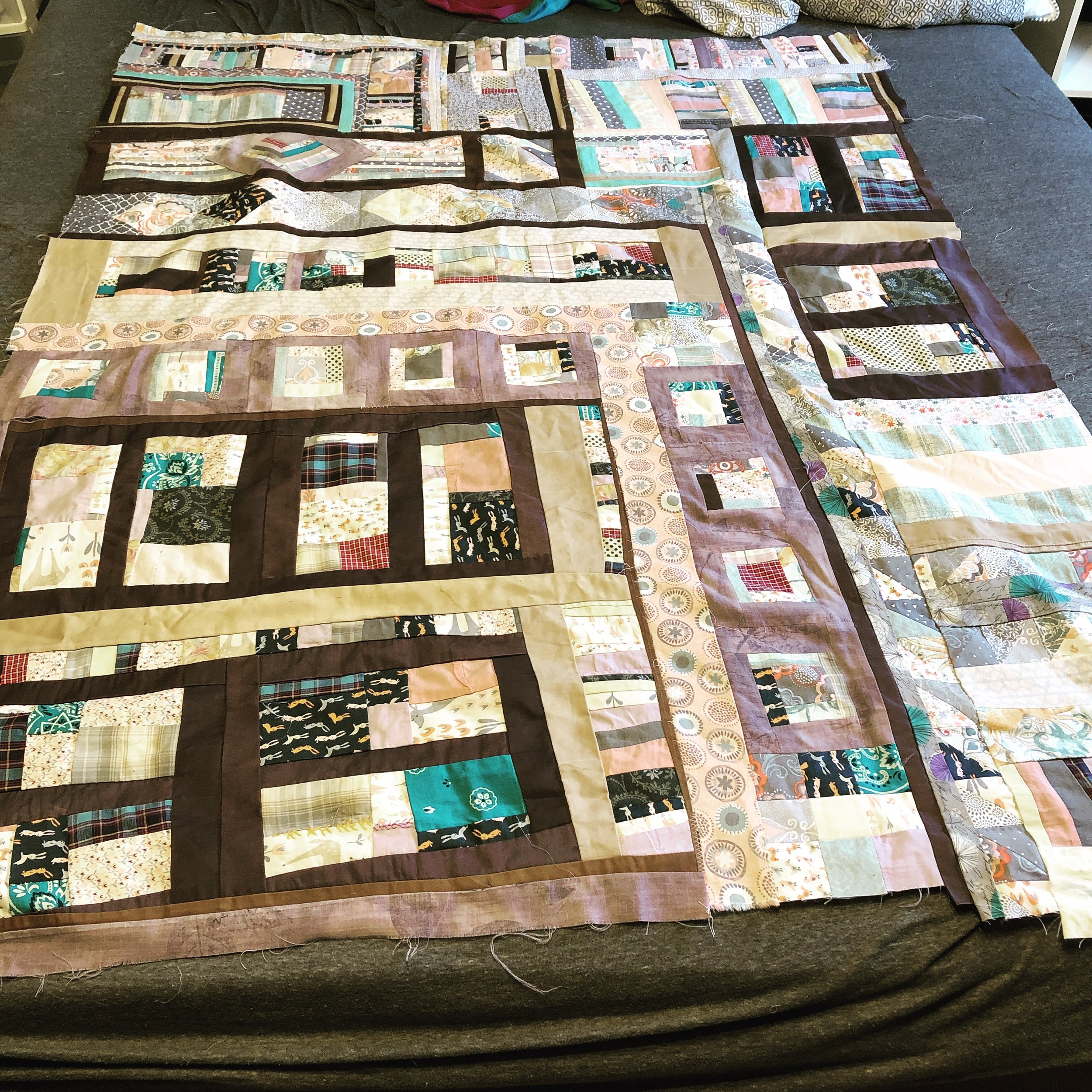 """[Image description: an improvised quilt top in mixed quilting & salvaged clothing fabrics, about 58"""" x 46"""" lying on top of a queen-sized bed.]"""