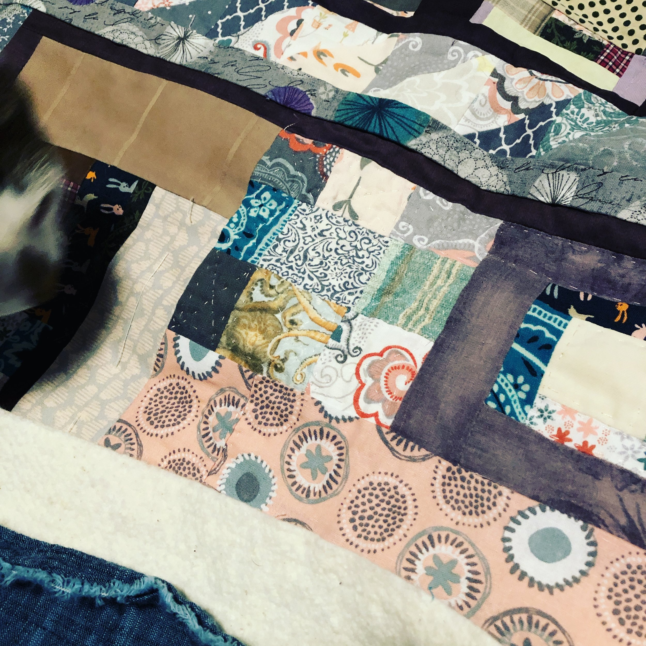 [Image description: a close-up of the same quilt top, now assembled with batting and backing, showing some hand-stitched quilting lines in a 9-patch block and a log cabin block. The face of a white and gray domestic short hair cat is just visible in the upper left.]