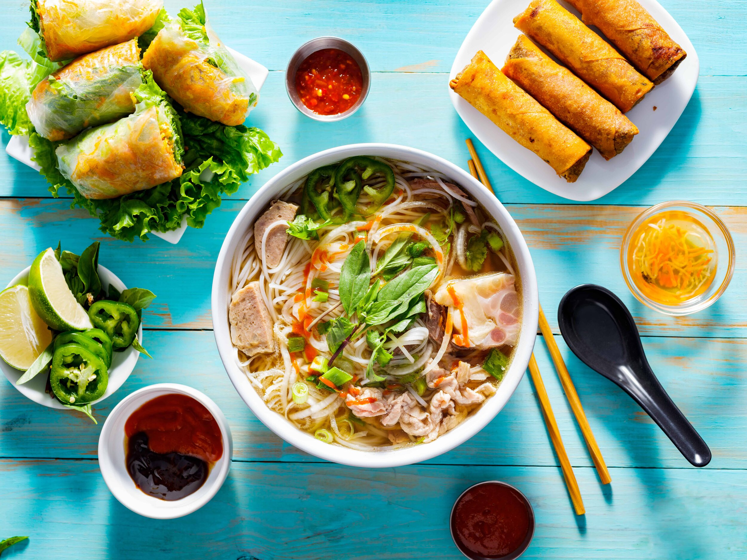 Canva - Vietnamese Pho Bo Soup with Appetizers on Table and Drizzled with Sriracha Sauce (1).jpg