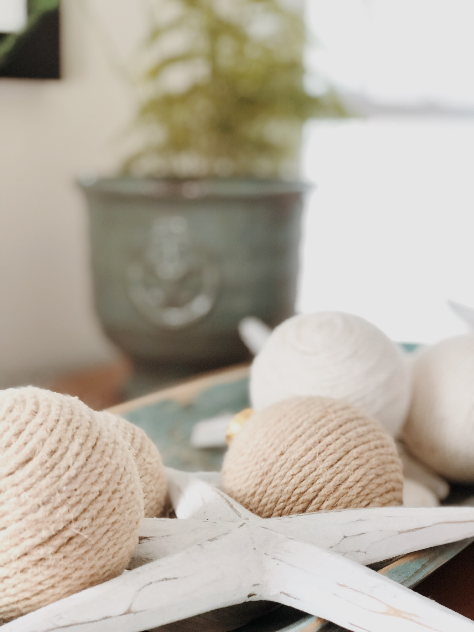 Handcrafted décor made with twine and displayed in a wooden bowl accentuates the casual design.