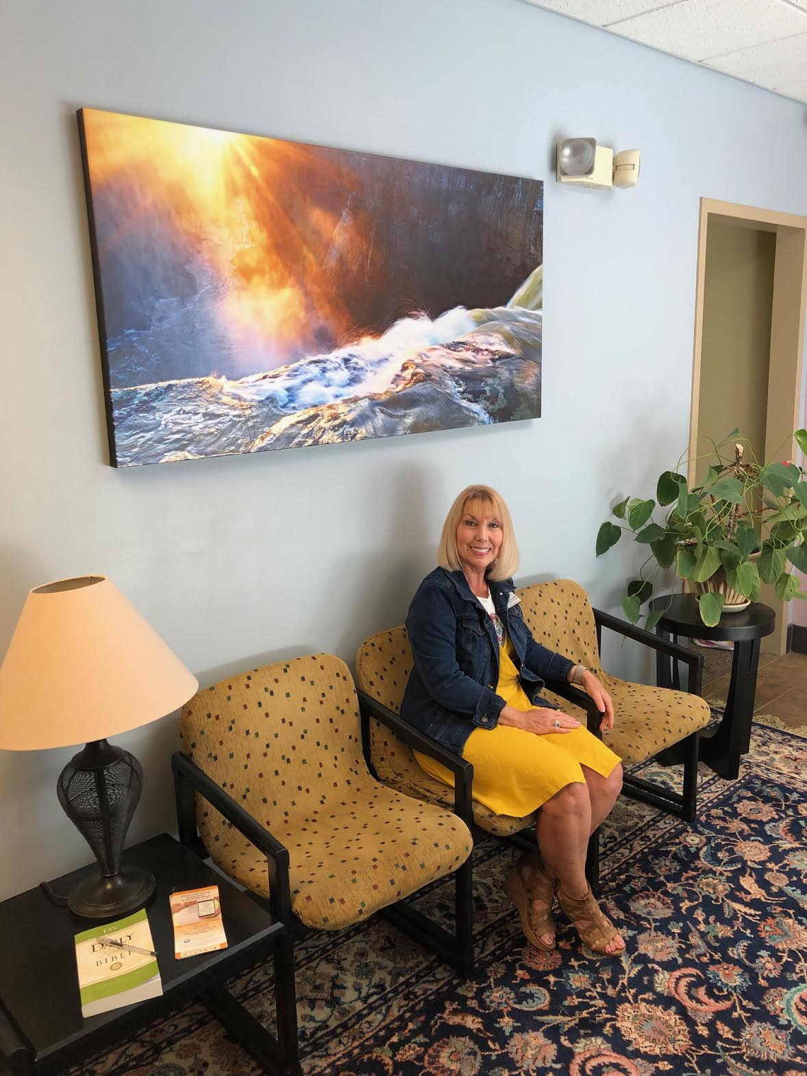 """Sharon Stauffer with 30x60 canvas of """"Sunset at the Falls"""" in the foyer at her office."""