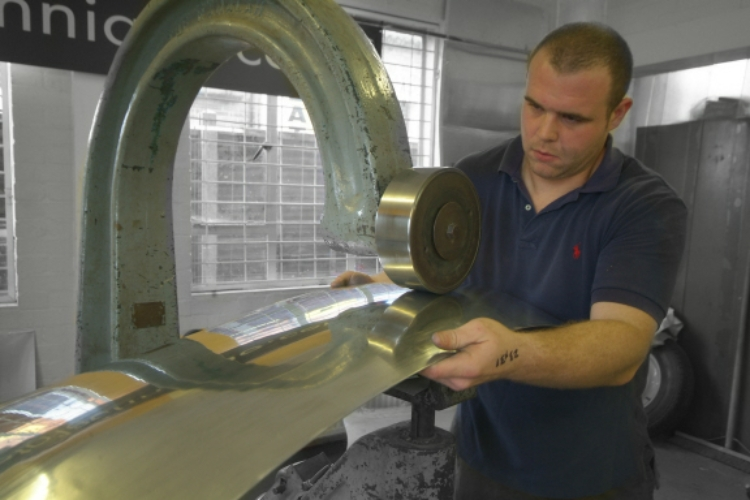 A skilled artisan using an old English wheel to produce a perfectly bespoke piece of bodywork.