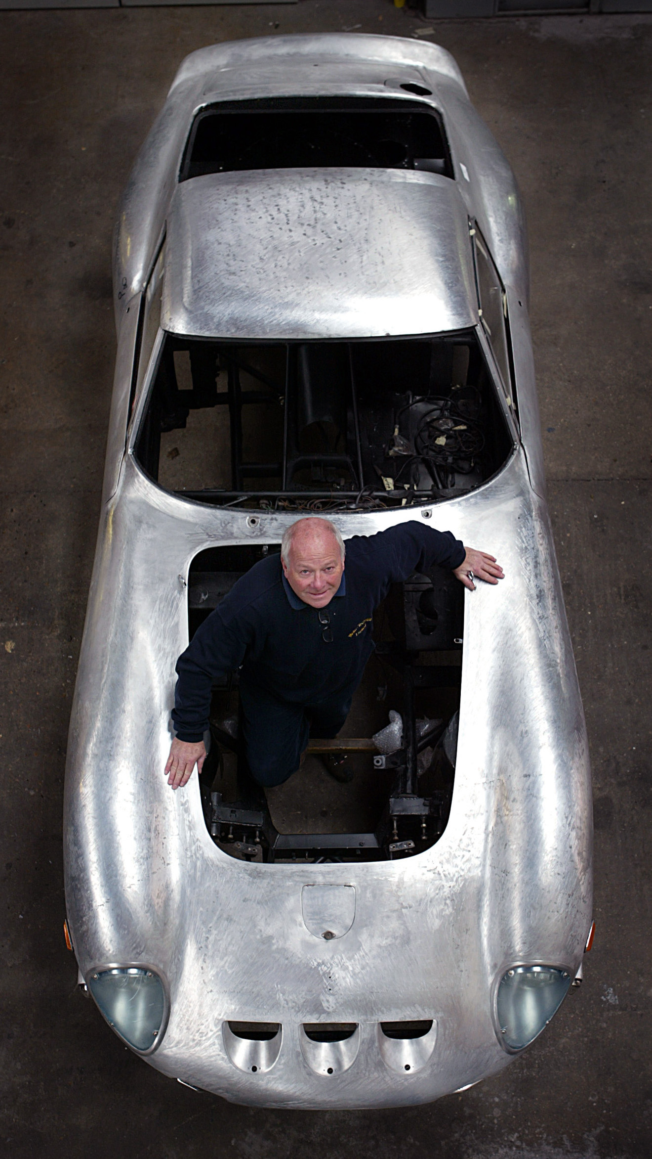 Kevin O'Rourke standing in the engine bay of the perfectly repaired and restored body shell of a Ferrari 250 GTO #3527 prior to it visiting the Moto Technique paint shop.