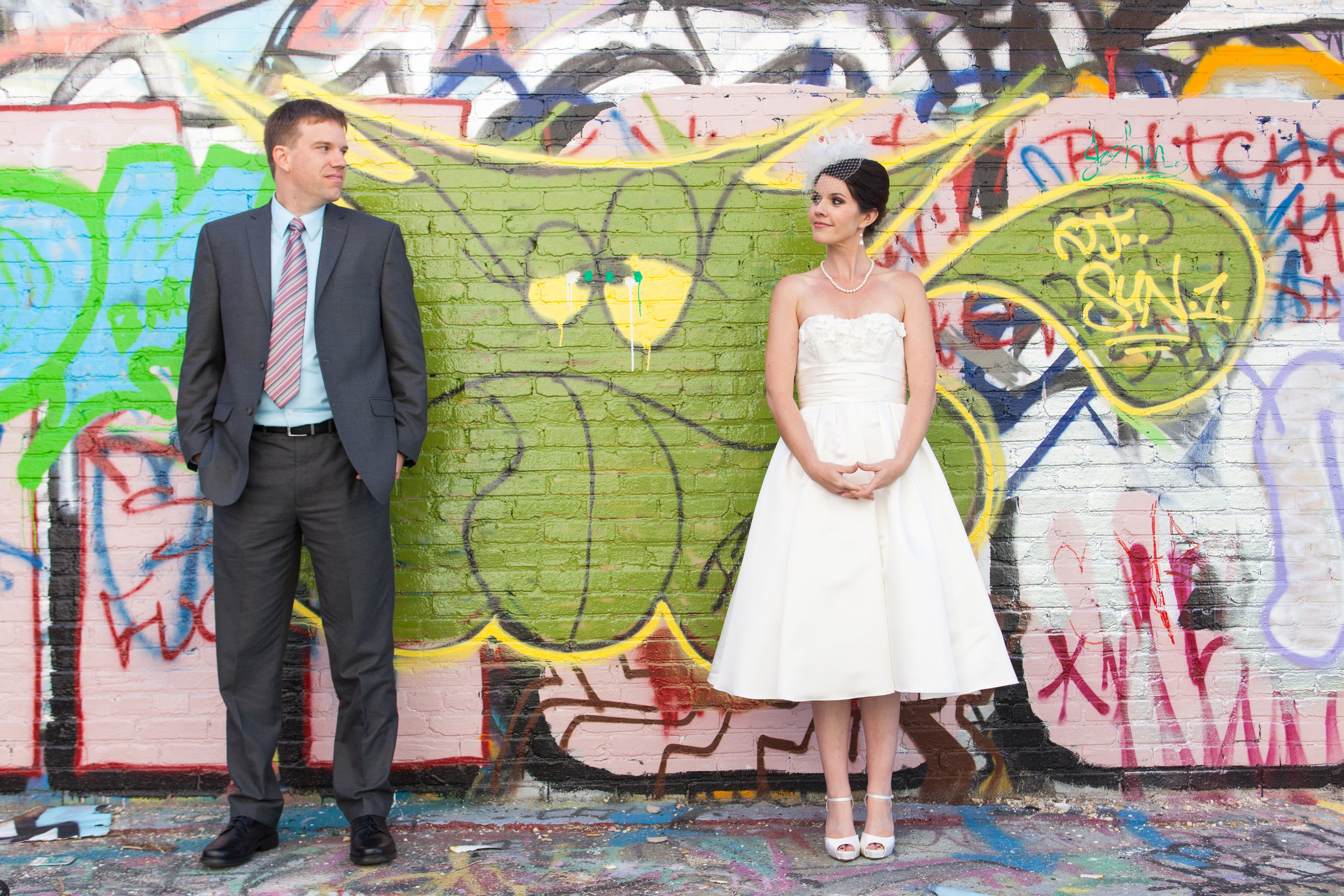 Bride & groom in front of graffiti wall